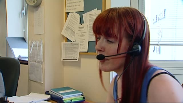 report reveals extent of female genital mutilation across england and wales t24061331 / tx int woman with headset speaking to nspcc helpline caller... - mutilazioni genitali femminili video stock e b–roll