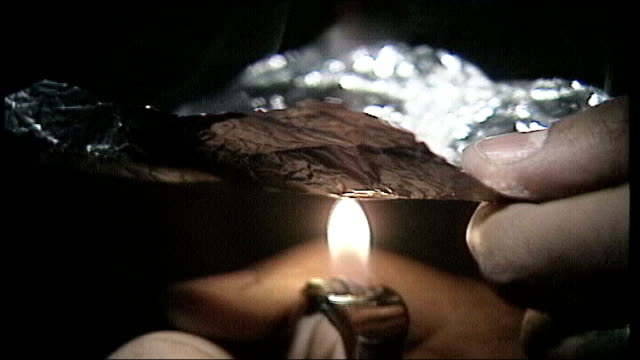 report says most drug use is 'harmless'; england: int drug being 'prepared' with tinfoil and lighter cannabis joint smoked tip of medical needle as... - smoked stock videos & royalty-free footage