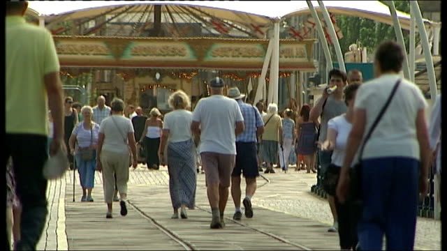 stockvideo's en b-roll-footage met report shows an ageing population puts a strain on welfare merseyside southport people to and fro along pier with merry go round in background bv... - southport engeland