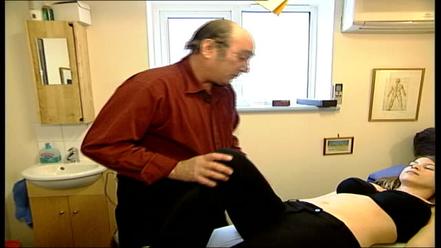 report states spinal manipulation is ineffective england london back view osteopath david charlaff examining female patient tresa zoom in patient's... - osteopath stock videos & royalty-free footage