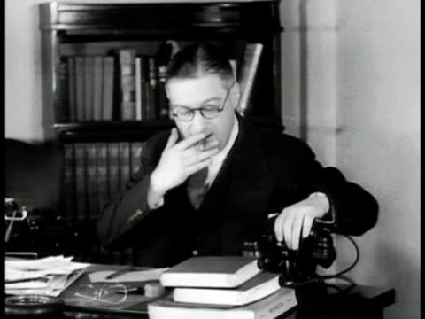 reporter calling in story from inside phone booth. arthur krock at desk in office talking on telephone seated at desk talking w/ assistant about why... - 1935 stock-videos und b-roll-filmmaterial