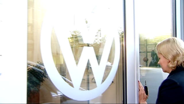 Reporter from car and chatting with Manager of car dealership Shadow from VW Logo on window inside showroom and rings from Audi logo on radiator...