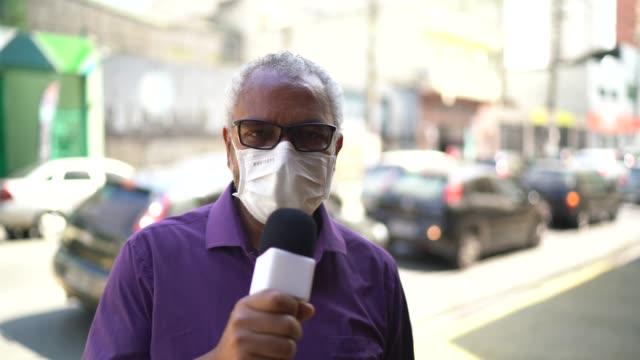vídeos de stock, filmes e b-roll de repórter de tv usando uma máscara facial falando com a câmera de gravação - journalist