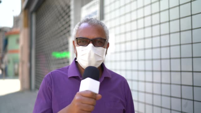 tv reporter man wearing a face mask talking to recording camera - tv reporter stock videos & royalty-free footage