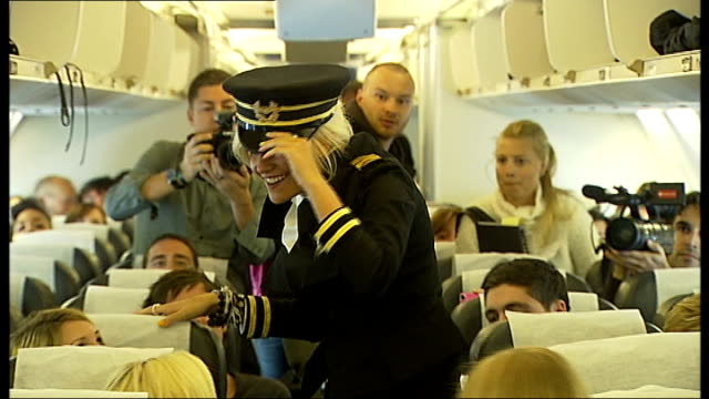 vidéos et rushes de reporter to camera, boeing 757 plane on tarmac painted with pixie lott brand int plane lott chatting to press lott speaking into microphone sot... - pixie lott