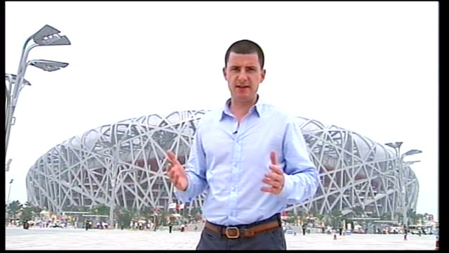 reporter to camera in front of beijing olympic stadium - bird's nest stock videos & royalty-free footage