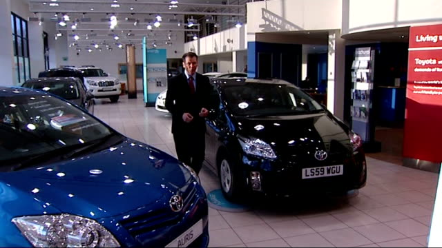 Reporter to camera in Toyota dealership showroom