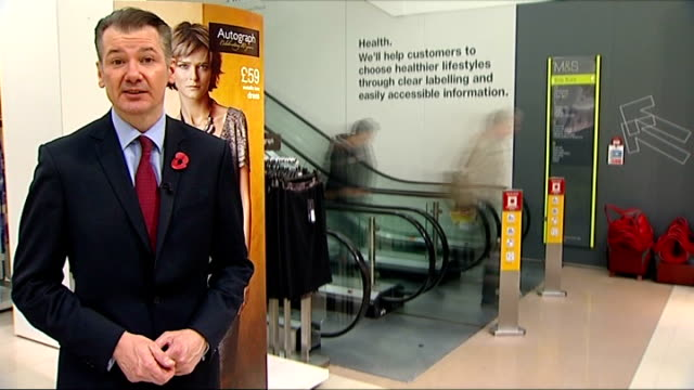 Reporter to camera next TIME LAPSE SPEEDED UP SEQ MS customers down escalator and along Women's wear department cardigans sign dresses hanging on...