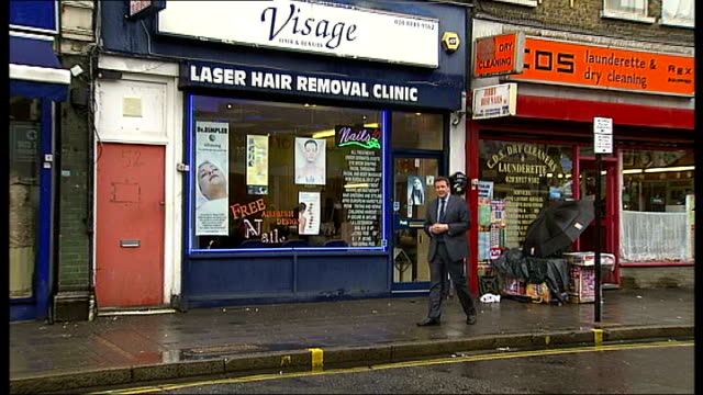 reporter to camera outside visage hair and beauty salon - anthropomorph stock-videos und b-roll-filmmaterial