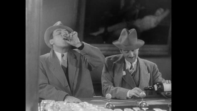 1931 reporter (pat o'brien) unconsciously drinks shots while arguing with his editor (adolph menjou) - 1931 stock videos & royalty-free footage