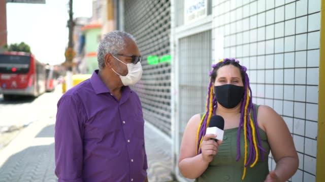 stockvideo's en b-roll-footage met de verslaggever die van tv een gezichtsmasker draagt dat een vrouw bij straat interviewt - media interview