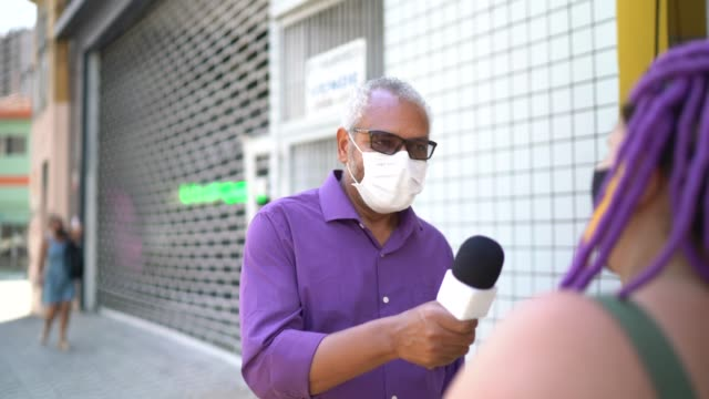 tv reporter wearing a face mask interviewing a woman at street - interview stock videos & royalty-free footage