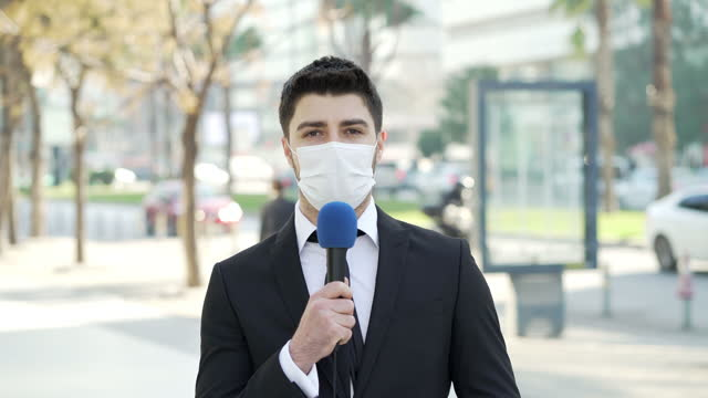 vídeos y material grabado en eventos de stock de reportero de televisión con una máscara facial - journalist