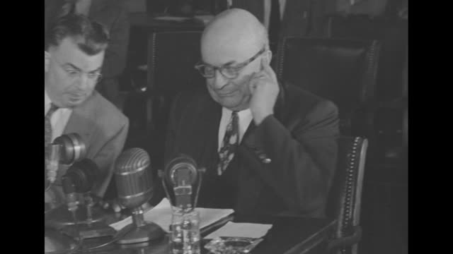 reporters and others focused on unseen sen. owen brewster, some writing / brewster surrounded by people writing except man beside him / brewster... - ハワード ヒューズ点の映像素材/bロール
