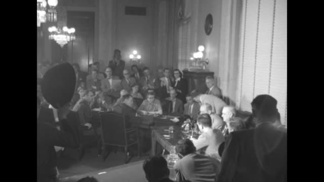 Reporters gathered in room for press conference / side view of Senate Armed Services Committee chairman Richard Russell Jr sitting at table in front...