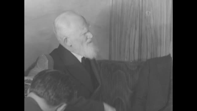 reporters gathered in room for press conference / two shots of george bernard shaw sitting on couch next to san francisco mayor angelo joseph rossi... - ジョージ バーナード ショー点の映像素材/bロール