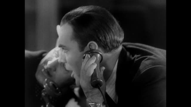 1931 reporters heads alternately fall into shot as they prepare to place scoop by phone - 1931 stock videos & royalty-free footage