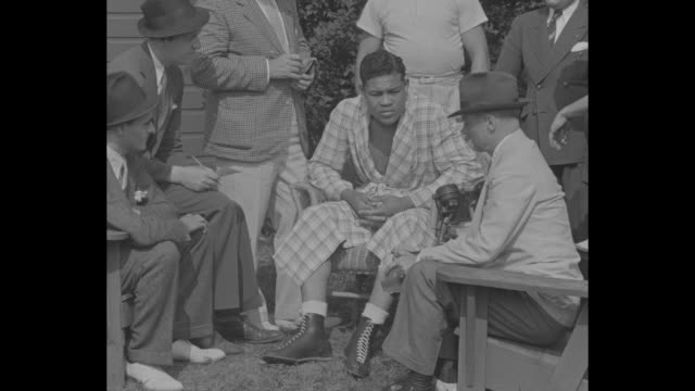vs reporters sit outdoors with boxer joe louis who wears a robe and ask him questions / reporters taking notes / reporters asking questions / cu... - 1936 stock videos and b-roll footage