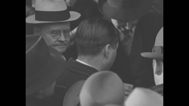 reporters wait outside door as defense attorneys frederick pope and lloyd fisher exit wearing hats and overcoats, they stand in door for photographs,... - オーバーコート点の映像素材/bロール