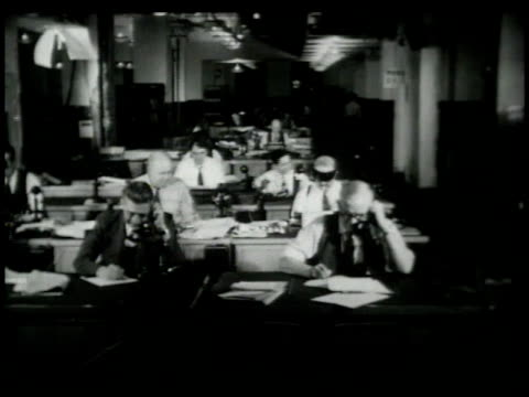 1948 MONTAGE Reporters working in busy news room / New York, New York, United States