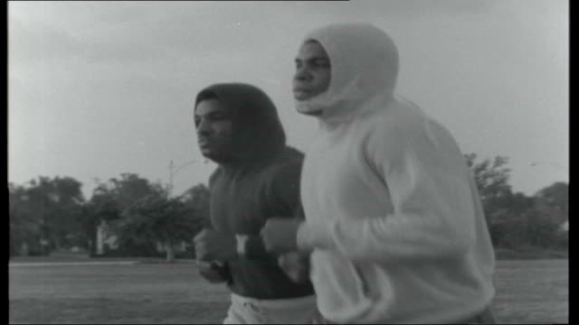 cassius clay / henry cooper training for world heavyweight title; usa: miami: mohammed ali training, shadow boxing, working out and jogging outside... - ボクシンググローブ点の映像素材/bロール