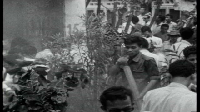 Indonesia Sukarno stripped of life Presidency Students climb up on PKI building Various of people standing about Students tearing leaflets posters...