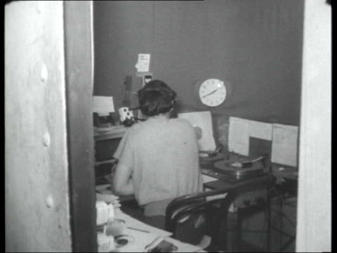 Pirate radio stations INT DJ inside studio broadcasting show SOT / 'Wot a Mess' sign on studio wall / DJs sitting down to meal Various of decks of...