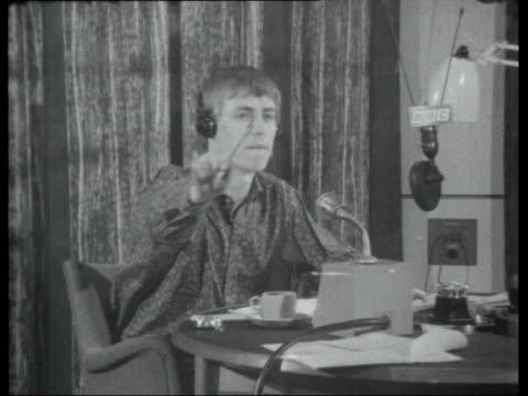 Pirate radio stations Studio clock / Simon Dee in studio / Dee smiling and gesturing as record plays SOT / Studio assistant selecting record from...