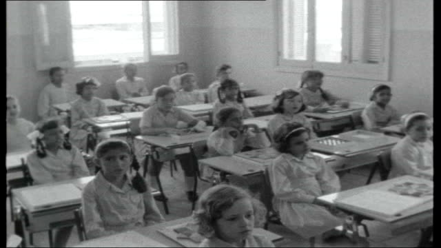 Saudi Arabia under King Faisal's rule INT SHOT along into classroom young schoolgirls sitting at desks and singing Prayer to King Faisal SOT
