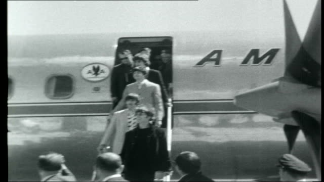 vídeos de stock e filmes b-roll de the beatles across america ext small crowd of teenagers on airport runway to greet beatles/ four beatles down aircraft steps past press and onlookers... - the beatles
