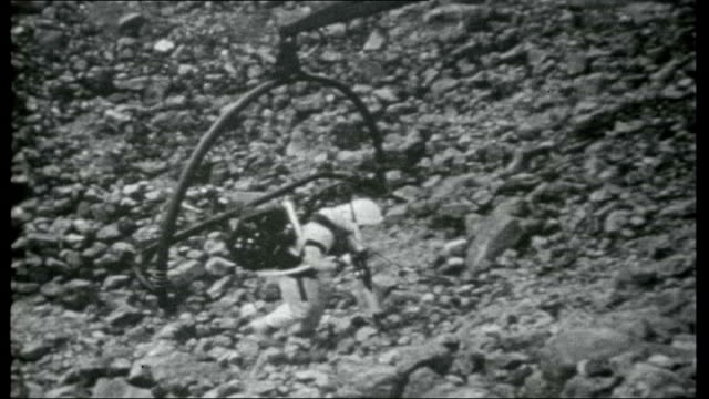 Apollo Moon Shot Texas Lunarnaut Training Centre Astronaut in training using harness and walking stick to move over simulated moon landscape /...