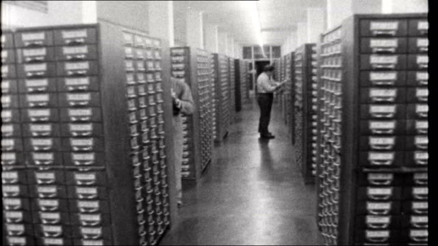 search for martin bormann west germany wiesbaden police headquarters police officer looking at file in rows of filing cabinets track back / police... - detective stock videos & royalty-free footage