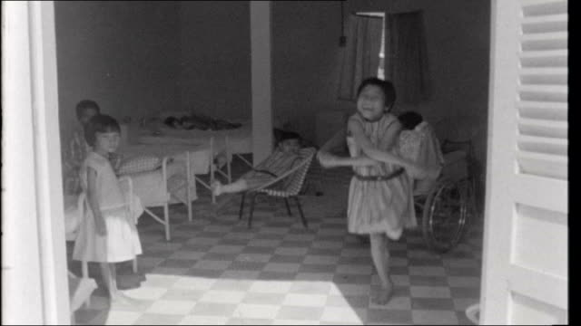 Vietnam Refugees Civilian War Victims INT Girl with amputation below the left knee skipping inside hospital day room / young boy with grenade wounds...