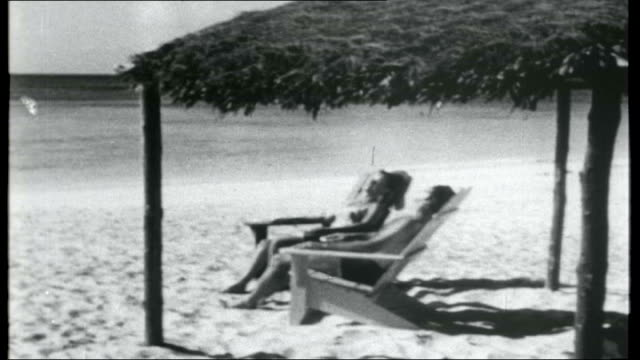 bahamas first negro government; bahamas: ext general view of sandy beach with palm trees / western woman sunbathing on lounger / two people... - bahamas stock videos & royalty-free footage
