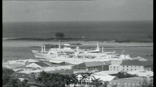 bahamas first negro government; nassau: * * music overlay sot * * general view of coastline / ocean liner moored / tourists / men sailing small... - bahamas stock-videos und b-roll-filmmaterial