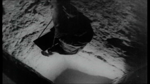 West Berlin FILE / 1965 INT Shots of tunnellers sitting eating at tunnel entrance / man being lowered into tunnel / tunneller lying on his back...
