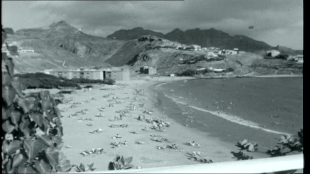 Aden YEMEN Aden EXT Reporter to camera / View of sea PAN to beach and mountains / People on beach / Steel net leading into sea / People playing in...