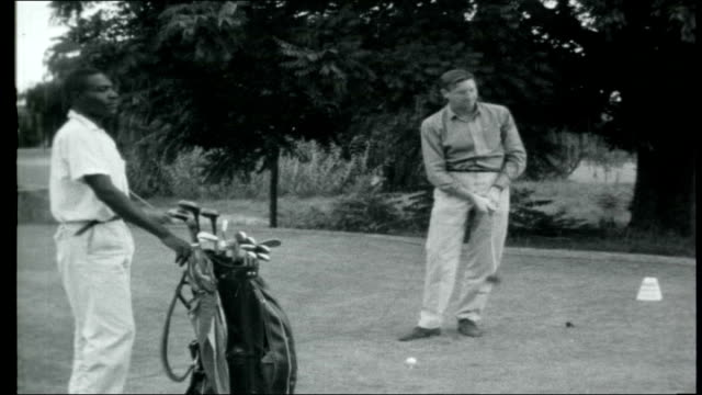 Rhodesia Britain enforces sanctions RHODESIA EXT Sandy Gall on golf course teeing up then hitting ball as watched by black caddy Reporter to camera...