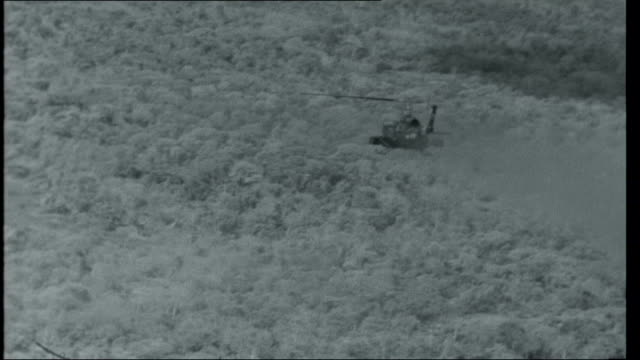 vietnam; mid air sequence pilot's hand using joystick, helicopter flying over forest area and firing, explosions on ground, close shots of crew,... - vietnamkriget bildbanksvideor och videomaterial från bakom kulisserna