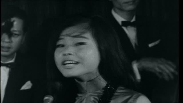 Vietnam Saigon at work and war INT Young Vietnamese woman singing Western pop song SOT