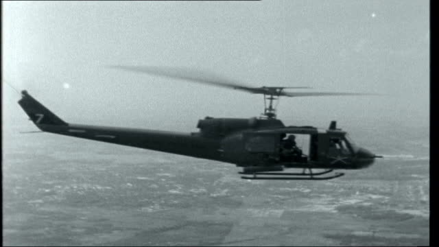 vietnam south air shots of bell us military helicopters of the 197th helicopter unit flying over south vietnam / crew members manning guns at open... - vietnam war stock videos & royalty-free footage