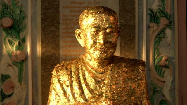 vídeos de stock e filmes b-roll de representative famous monk statue with gold leaf - modelo objeto