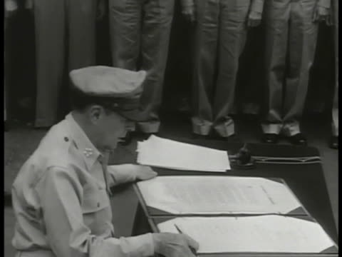 Representatives of Allied Powers standing Supreme Allied Commander US Army General MacArthur signing Japanese Instrument of Surrender document End of...