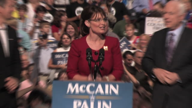 Republican Governor Sarah Palin speaking at podium during presidential campaign with her husband Todd Palin at left and US Senator John McCain at...