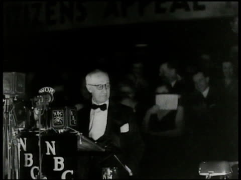 Republican leader Herbert Hoover working for the party walking w/ people near train dressed in tuxedo standing w/ three unidentified men on stage w/...