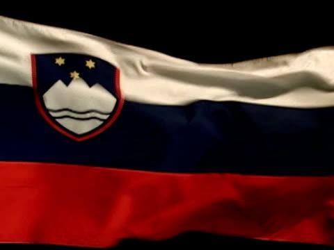 republika slovenija country flag flying against black bg. three horizontal bands white, blue, red w/ slovenian seal in upper hoist area on white &... - white点の映像素材/bロール