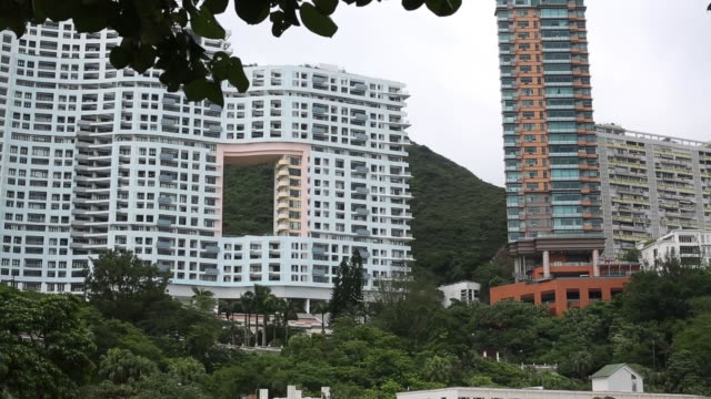 Repulse Bay beach in Hong Kong showing people on beach and highrise properties behind Wide shot bathers on beach and residential apartment blocks...