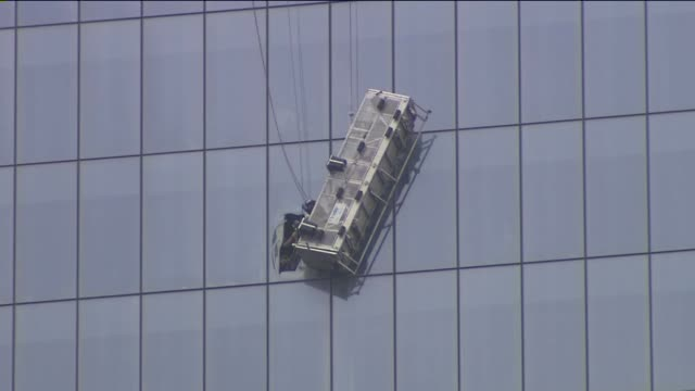 rescue crews cut through a window on the 69th floor of 1 world trade center and pulled to safety two workers who dangled high above the ground 90... - window washer stock videos & royalty-free footage