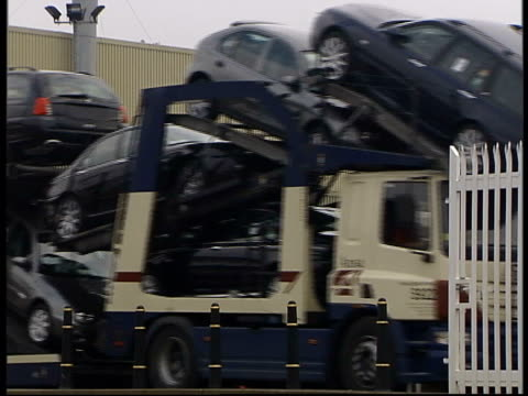vídeos de stock, filmes e b-roll de rescue deal; england birmingham longbridge ext gv 'mg rover group' sign tilt down & to rover plant entrance lms car transporter, carrying new rover... - carrying
