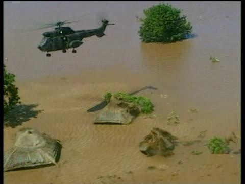 vídeos de stock e filmes b-roll de rescue helicopter down draft blows away thatched roofs mozambique floods; mar 00 - telhado de palha